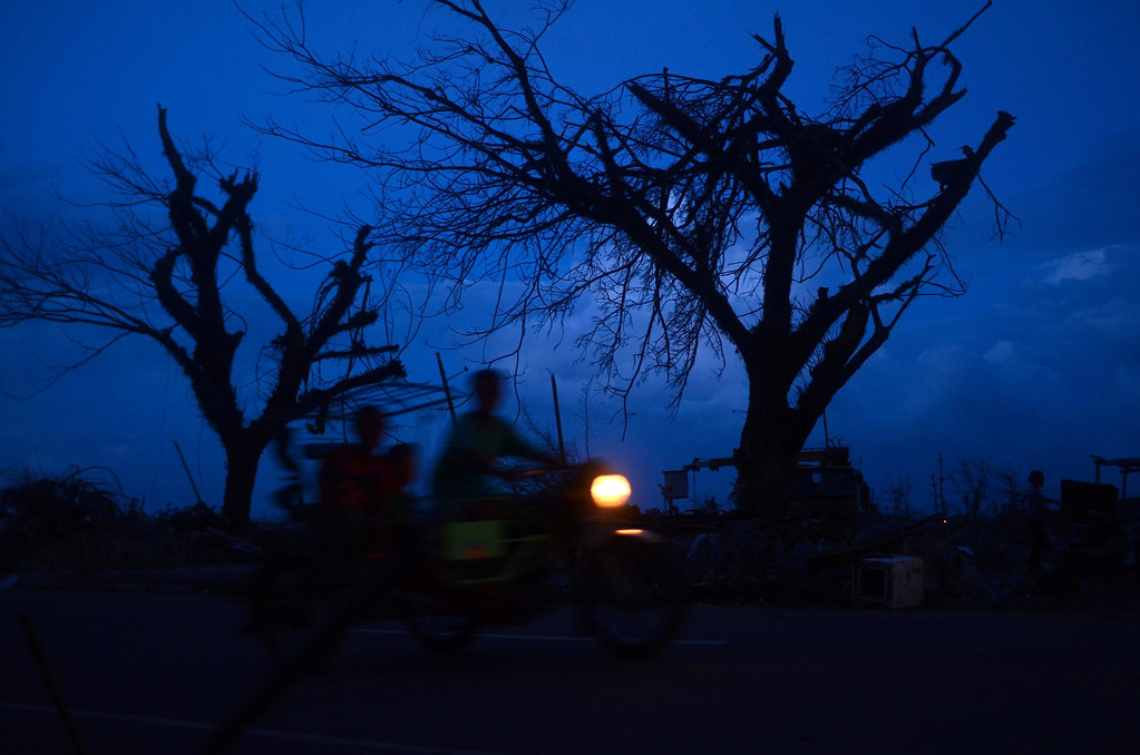 . A motorcycle passes by a road following the recent super typhoon on November 21, 2013 in Tacloban, Leyte, Philippines.  (Photo by Dondi Tawatao/Getty Images)
