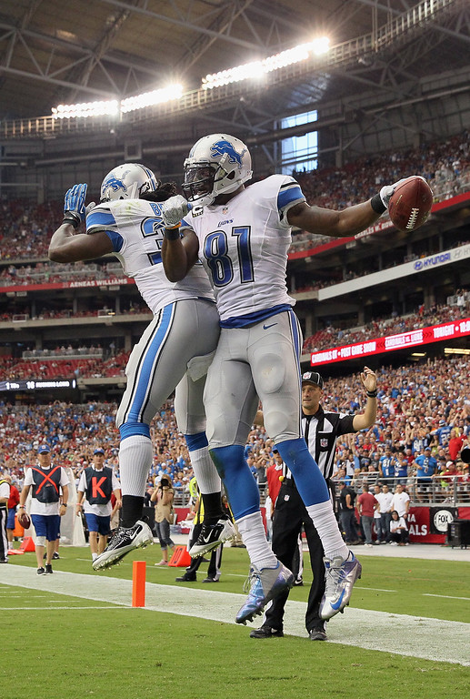 . Wide receiver Calvin Johnson #81 of the Detroit Lions and running back Joique Bell (L) #35 celebrate Johnson\'s second touchdown of the first half against the Arizona Cardinals at University of Phoenix Stadium on September 15, 2013 in Glendale, Arizona.  (Photo by Jeff Gross/Getty Images)