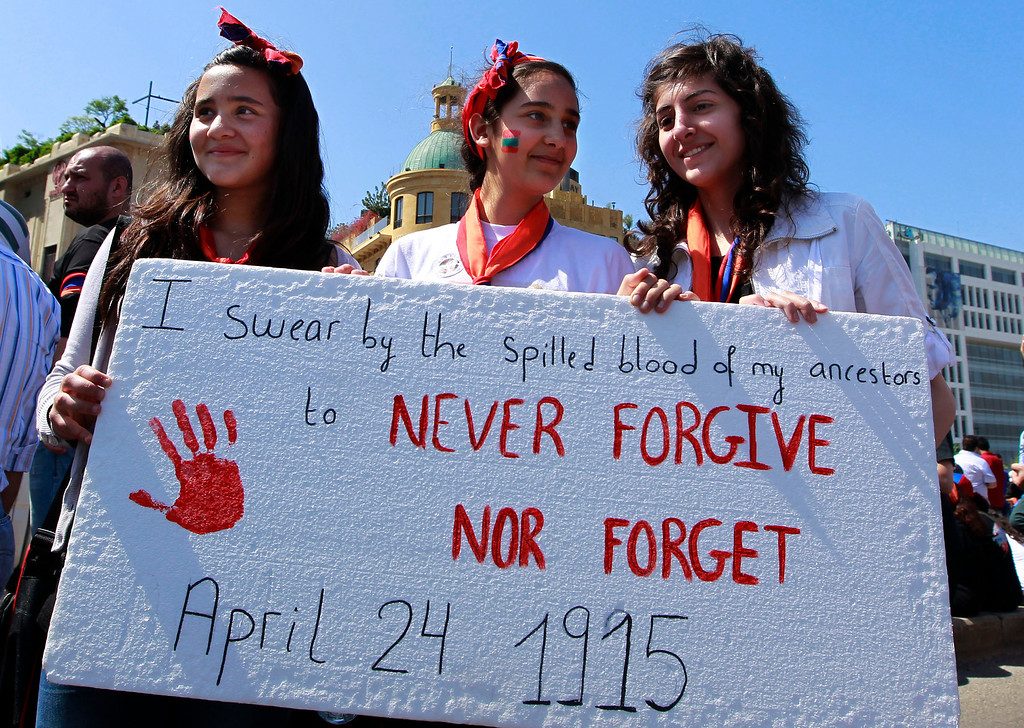 . Lebanese Armenian girls hold a poster during a rally marking the 98th anniversary of massacres on thousands of Armenians, in Beirut, Lebanon, Wednesday, April 24, 2013. Armenian communities around the world mark the killing of up to 1.5 million Armenians, on April 24 each year with marches, vigils and rallies to demand recognition from the world community, and reparations from Turkey. Turkey claims the number of deaths is inflated and says the victims were killed in civil unrest. (AP Photo/Bilal Hussein)