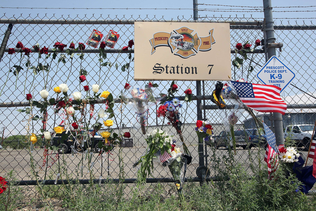 ". A memorial of flowers and flags forms outside of the Granite Mountain Hotshot Fire Station 7 in Prescott, Arizona July 1, 2013.  Reinforcements poured in Monday to battle a runaway wildfire which quadrupled in size overnight after killing 19 firefighters in one of the worst such incidents in US history. The Yarnell Hill fire -- which killed all but one member of a 20-strong ""hotshot\"" team -- was the biggest loss of firefighters\' lives since the September 11 attacks, and the most from a US wildfire in 80 years.   Krista Kennell/AFP/Getty Images"