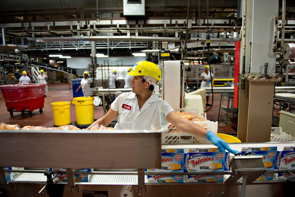. A bakery employee works on the packing line of Twinkies snack cakes at a Hostess Brands LLC bakery in Schiller Park, Illinois, U.S., on Monday, July 15, 2013. Photographer: Daniel Acker/Bloomberg