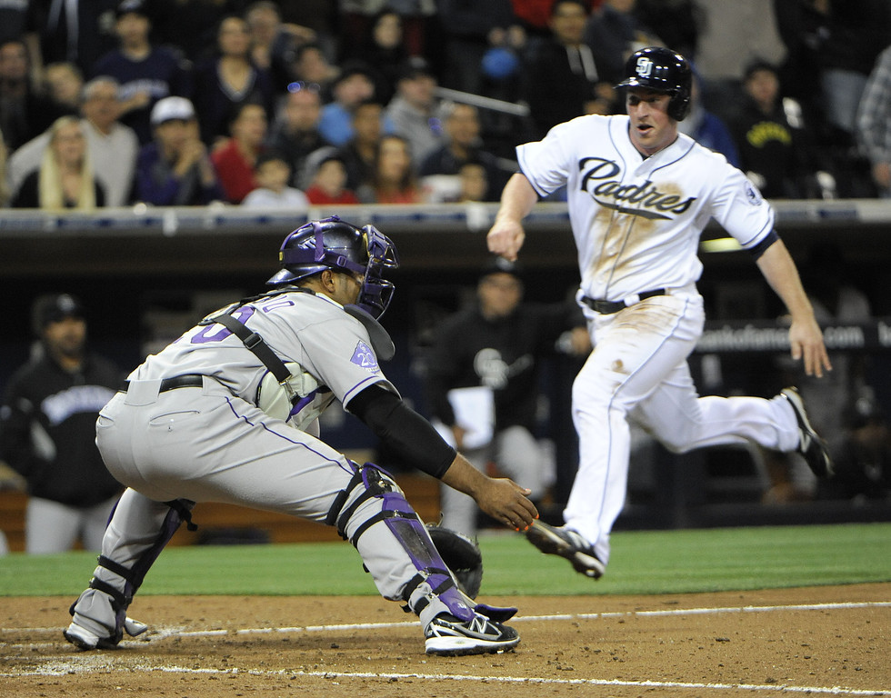 . SAN DIEGO, CA - APRIL 12:  Jedd Gyorko #9 of the San Diego Padres scores ahead of the tag of Wilin Rosario #20 of the Colorado Rockies in the seventh inning of a baseball game at Petco Park on April 12, 2013 in San Diego, California.  (Photo by Denis Poroy/Getty Images)