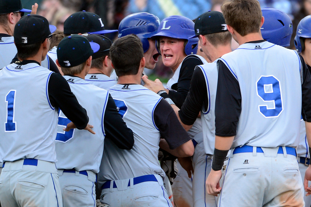 . LAKEWOOD, CO - MAY 23: Longmont\'s Andrew Baldt celebrates his grand-slam home run with teammates. The Longmont Trojans take on the Niwot Cougars in the 4A Baseball State Semi-Final Championships. (Kathryn Scott Osler, The Denver Post)