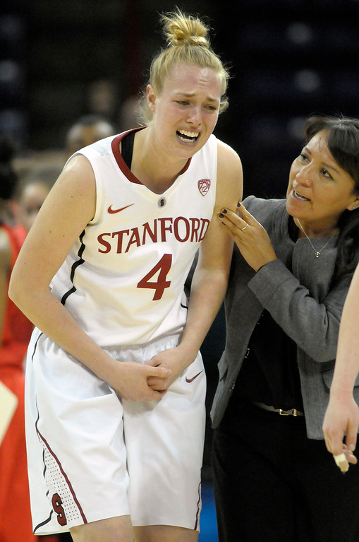 . Stanford\'s Taylor Greenfield (4) leaves the court with a hand injury during the first half of Stanford\'s game against Georgia in a regional semifinal in the NCAA women\'s college basketball tournament, Saturday, March 30, 2013, in Spokane, Wash. (AP Photo/Jed Conklin)