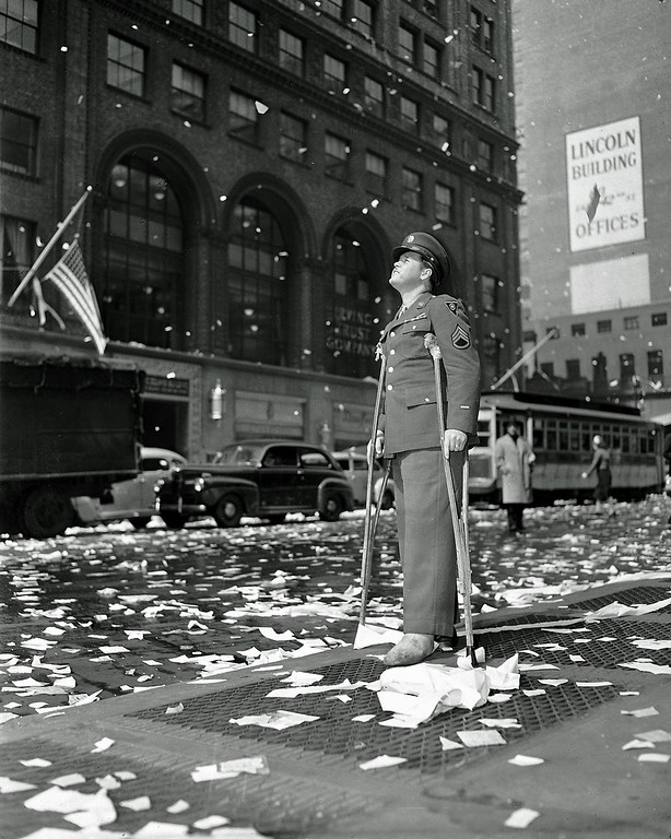 . Staff Sgt. Arthur Moore of Buffalo, N.Y., who was wounded in Belgium, stands on 42nd Street near Grand Central Station in New York Monday, May 7, 1945 as New Yorkers celebrate news of VE Day, victory over Nazi Germany.  (AP Photo)