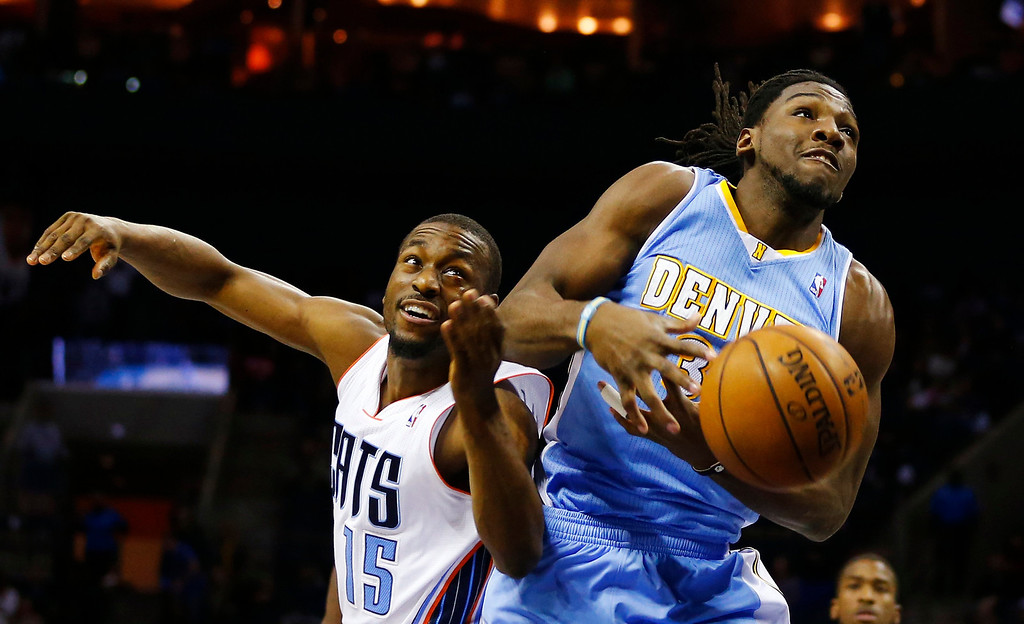 . Denver Nuggets small forward Kenneth Faried (35) loses control of the ball against Charlotte Bobcats point guard Kemba Walker (15) during the first half of their NBA basketball game in Charlotte, North Carolina February 23, 2013. REUTERS/Chris Keane