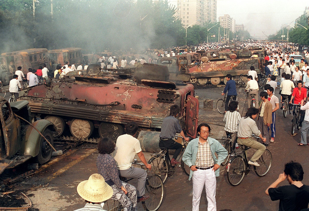 . Beijing residents inspect the interior of some of over 20 armored personnel carriers burned by demonstrators to prevent the troops from moving into Tiananmen Square 04 June 1989.  (MANUEL CENETA/AFP/Getty Images)