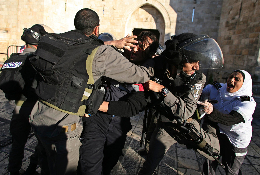 . Israeli border policemen scuffle with Palestinian medics (C and R) during clashes at a protest, held without a police permit, outside Jerusalem\'s Old City April 2, 2013. The protest took place following the death of Maysara Abu Hamdeya, a Palestinian inmate who died from cancer in an Israeli hospital on Tuesday. Hamdeya\'s death also threatened to raise tensions in the Israeli-occupied West Bank, where Palestinians, who view jailed brethren as heroes in a fight for statehood, have held several protests in recent weeks in support of prisoners. REUTERS/Muammar Awad