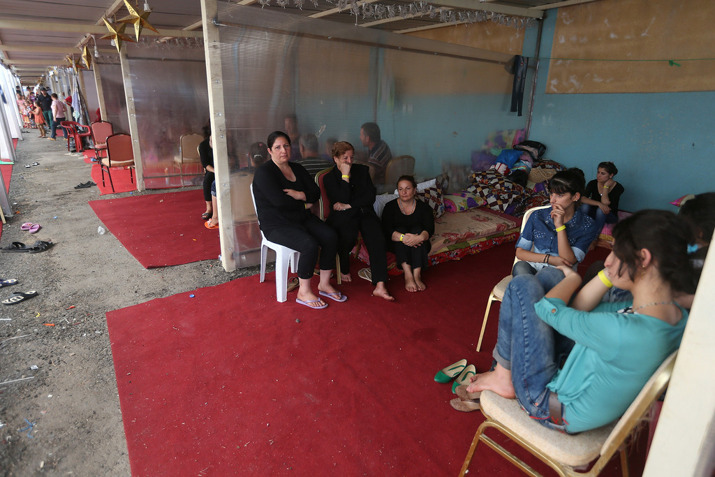 . Displaced Iraqi Christian families who fled from the Christian village of Hamdania near Mosul province in Iraq, sit at a temporary shelter for the displaced Christian families, in Ainkawa, a suburb of Irbil, with a majority Christian population, Iraq, Friday, June 27, 2014. Around 2,000 Christians had entered the Kurdish city of Irbil by Thursday morning, June 26. A Christian official there said the Kurdish region is the only part of Iraq where Christians are protected from violence. (AP Photo/Hussein Malla)