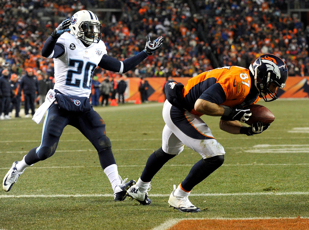 . Denver Broncos wide receiver Eric Decker (87) catches the ball in the end zone for a fourth quarter touchdown as Tennessee Titans cornerback Alterraun Verner (20) throws his hands up.   (Photo by Joe Amon/The Denver Post)