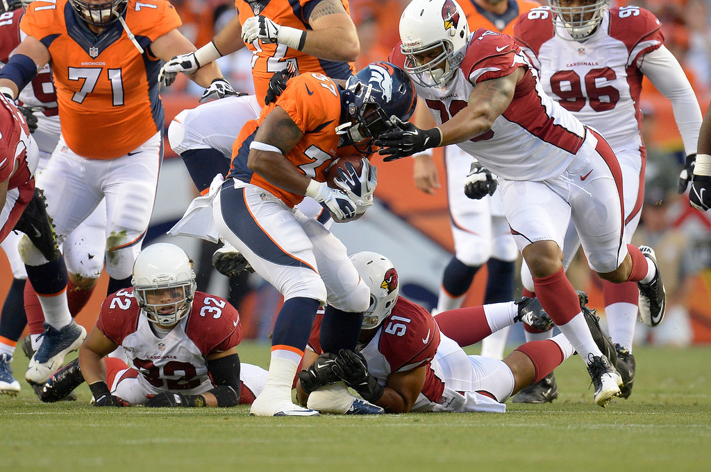 . Denver Broncos running back Jeremiah Johnson (37) is tackled by Arizona Cardinals linebacker Kevin Minter (51) and defensive tackle David Carter (79) during the first half on August 29, 2013 at Sports Authority Field at Mile High.  (Photo by John Leyba/The Denver Post)