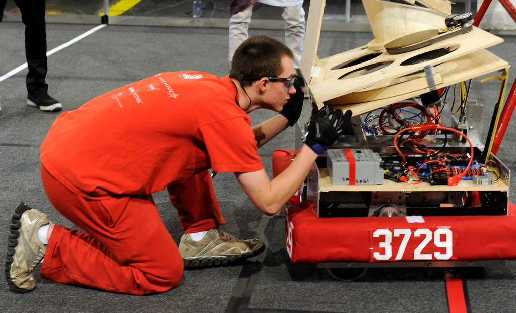 . DENVER, CO.- APRIL 6: Regis Jesuit High School Pit crew member Chris Morroni makes final adjustments on the robot after it is placed on the competition floor. The Colorado Regional FIRST Robotics Competition takes place in Magness Arena inside the Ritchie Center on the University of Denver campus. High School students from all over the state, region, and even a team from Mexico, participate in a high-tech spectator sporting event (this year the teams used frisbees) using specially engineered robots that are maneuvered by human drivers using computers and joy sticks.(Photo By Kathryn Scott Osler/The Denver Post)