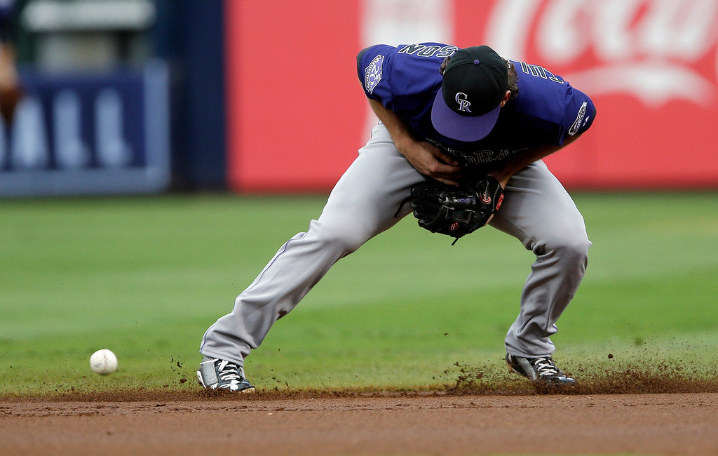 . Colorado Rockies second baseman Charlie Culberson boots a ground ball from Atlanta Braves\' Jason Heyward in the first inning of a baseball game in Atlanta,  Wednesday,  July 31, 2013. (AP Photo/John Bazemore)