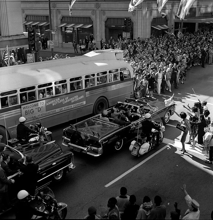 . An open limousine carrying the president and first lady approaches the intersection of Main and Ervay streets in Dallas as the presidential motorcade approaches Dealey Plaza. Texas Gov. John Connally and wife Nellie are seated in the limousine\'s jump seats.