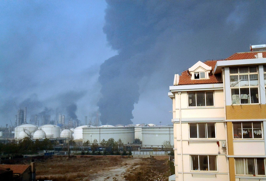 . Smoke rises from oil refineries after explosion in Qingdao in east China\'s Shandong province, Friday, Nov. 22, 2013. The oil pipeline owned by China\'s largest oil refiner, Sinopec, ruptured and while being repaired caught fire and exploded, killing many people and injuring others, a district government in the port city of Qingdao said. (AP Photo)