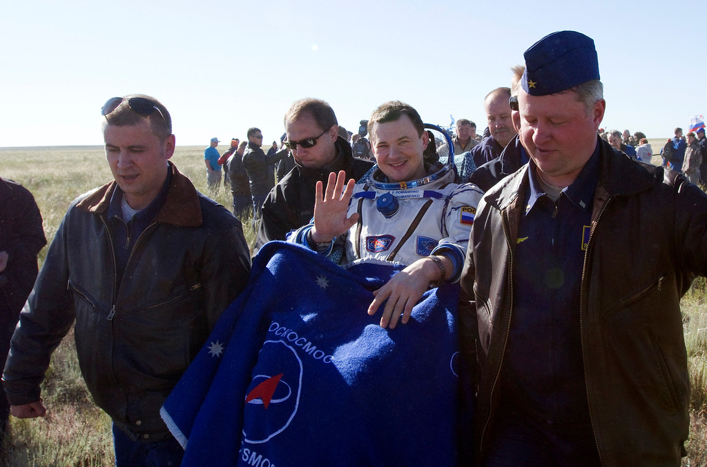 . Russian cosmonaut Roman Romanenko waves as Russian space agency, Roskosmos, ground personnel carry him shortly after the landing aboard the Russian Soyuz space capsule some 150 km (90 miles) southeast of the town of Zhezkazgan in central Kazakhstan on May 14, 2013.  AFP PHOTO / POOL / SERGEI REMEZOV/AFP/Getty Images