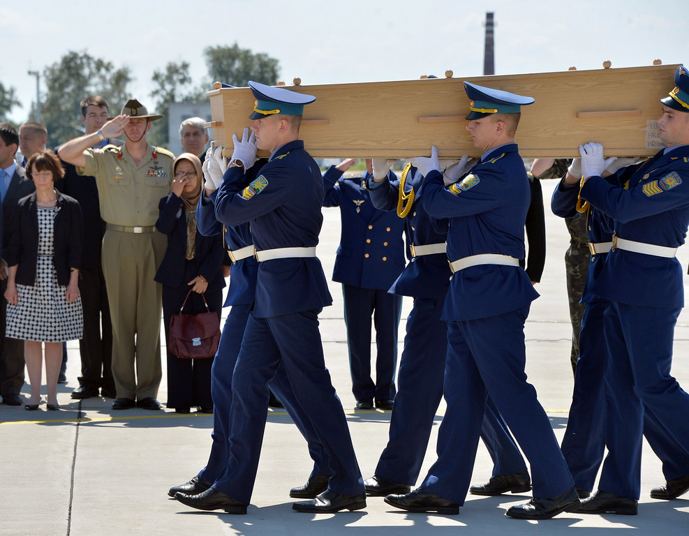 . Ukrainian soldiers carry a coffin with the remains of a victim of the Malaysia Airlines flight MH17 crash to a military plane during a ceremony at the airport of Kharkiv, Ukraine, on July 23, 2014. The first plane carrying bodies from downed Malaysia Airlines flight MH17 left eastern Ukraine for the Netherlands on July 23 following a sombre ceremony. The Dutch military aircraft took off from the airport in the government-controlled city of Kharkiv bound for Eindhoven after the first group of victims\' remains were loaded onto the plane in wooden coffins.   AFP PHOTO/ GENYA SAVILOV/AFP/Getty Images