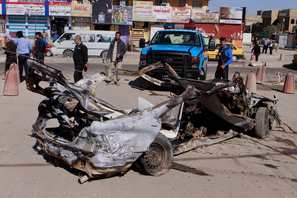 . Iraqi security forces inspect the scene of a car bomb attack in the Shiite stronghold of Sadr City, Baghdad, Iraq, Tuesday, March 19, 2013.  (AP Photo/ Karim Kadim)