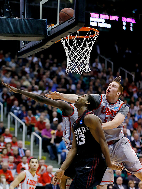 . New Mexico\'s Alex Kirk, right, tries to block the shot of Harvard\'s Wesley Saunders in the first half during a second-round game in the NCAA college basketball tournament in Salt Lake City, Thursday, March 21, 2013. (AP Photo/George Frey)