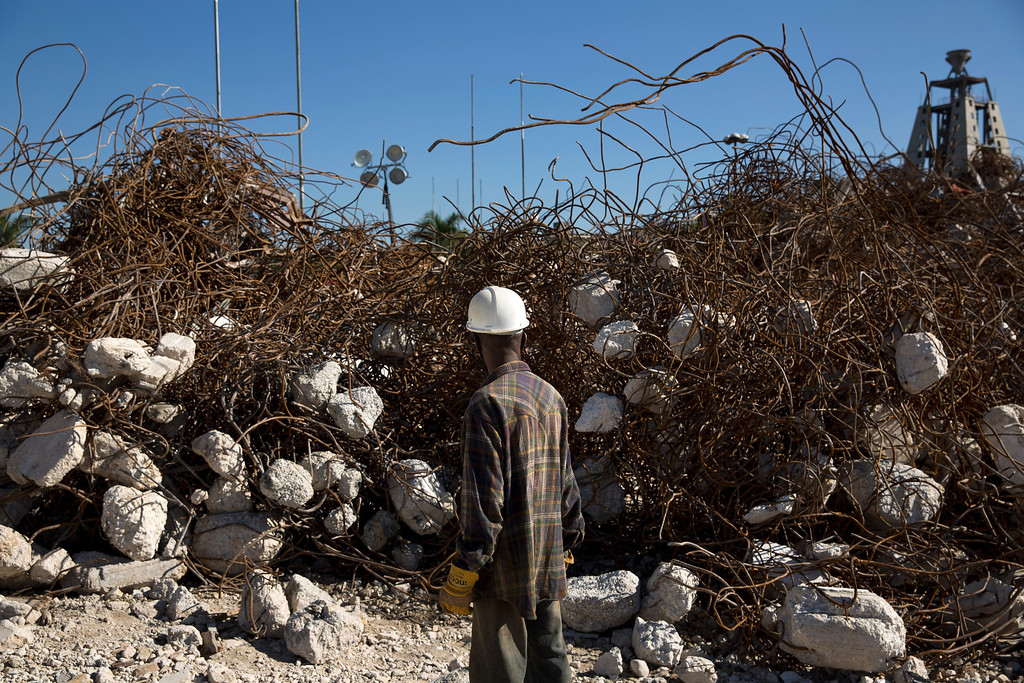 . A worker in front of twisted and tangled iron rebar where the presidential palace, destroyed in the 2010 earthquake and only recently demolished, once stood, in Port-au-Prince, Haiti, Dec. 5, 2012. Despite billions of dollars spent -- and billions more allocated for Haiti but unspent -- post-earthquake reconstruction has barely begun and more than 350,000 Haitians still languish in nearly 500 tent camps. (Damon Winter/The New York Times)