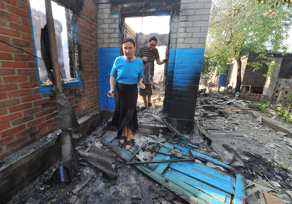 . Local residents walk near a house destroyed during a night combat between Ukrainian troops and armed pro-Russian militants in the village of Semenovka, near the eastern Ukrainian city of Slavyansk, on May 23, 2014. AFP PHOTO/ VIKTOR  DRACHEV/AFP/Getty Images