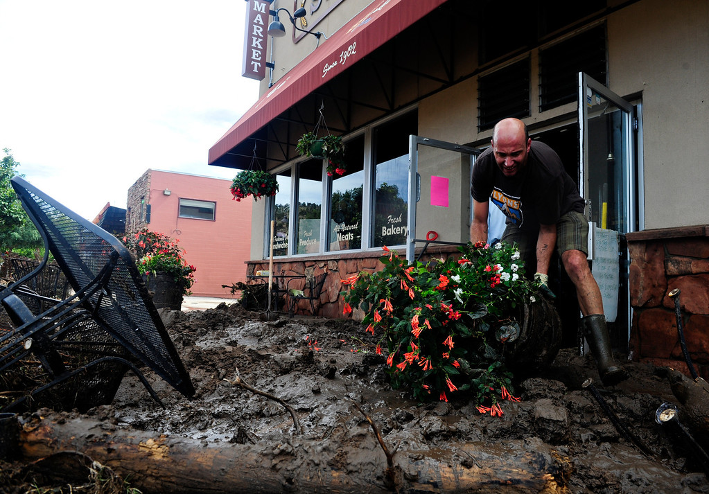 . Gary Seifert clears debris from the St. Vrain Market in Lyons Friday, Sept. 13, 2013. (Greg Lindstrom/Times-Call)