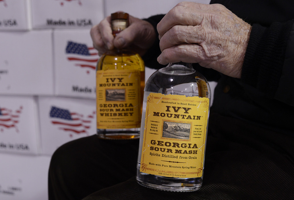 . Carlos Lovell, 85, holds bottles of the corn sour mash whiskey he helped create at the Ivy Mountain Distillery in Mt. Airy, Georgia, USA, 26 February 2013. The Lovell family began distilling the once illegal moonshine 150 years ago in the north Georgia mountains. Carlos and Fred learned how to make moonshine when they were teenagers, and continued making the 95 proof spirits until the early 1960s, but now have resumed their craft legally.  EPA/ERIK S. LESSER