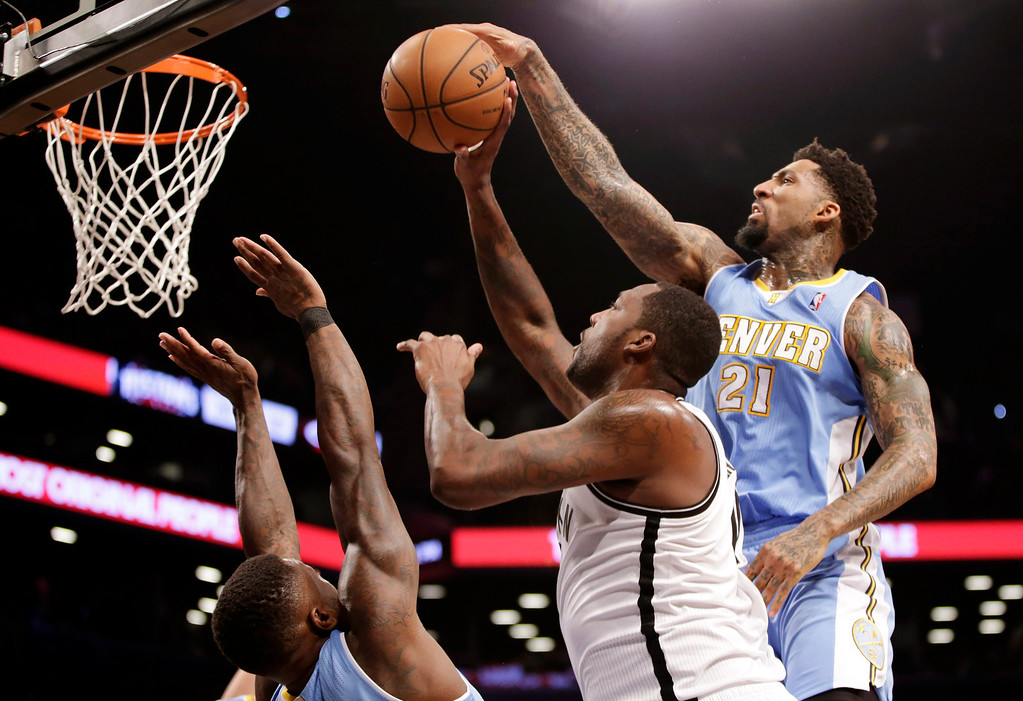 . Denver Nuggets forward Wilson Chandler (21) strips the ball from Brooklyn Nets center Andray Blatche, center, in the first half of an NBA basketball game Tuesday, Dec. 3, 2013, in New York. (AP Photo/Kathy Willens)