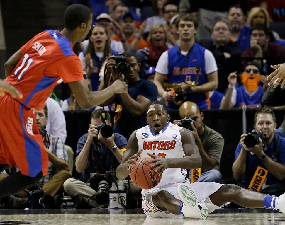 . Florida forward Dorian Finney-Smith (10) looks to pass as Dayton guard Scoochie Smith (11) looks on during the second half in a regional final game at the NCAA college basketball tournament, Saturday, March 29, 2014, in Memphis, Tenn. (AP Photo/Mark Humphrey)