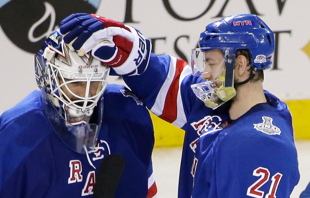 . New York Rangers center Derek Stepan (21) congratulates goalie Henrik Lundqvist after the Rangers beat the Los Angeles Kings 2-1 in Game 4 of the NHL hockey Stanley Cup Final, Wednesday, June 11, 2014, in New York. (AP Photo/Frank Franklin II)