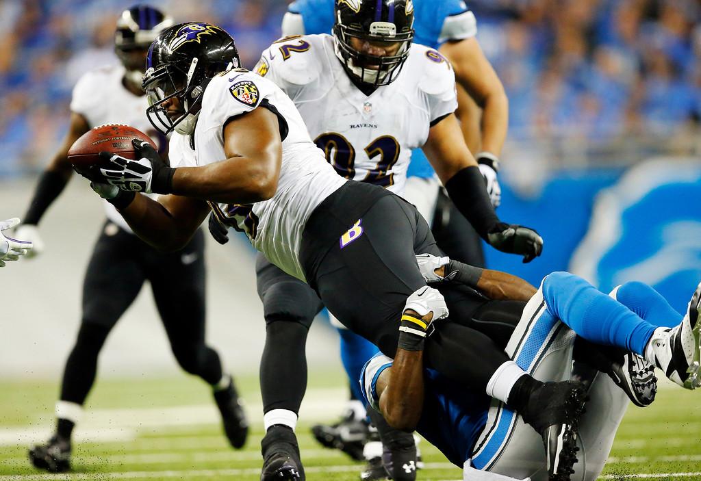. Baltimore Ravens defensive end DeAngelo Tyson, left, intercepts a pass intended for Detroit Lions running back Reggie Bush during the third quarter of an NFL football game in Detroit, Monday, Dec. 16, 2013. (AP Photo/Paul Sancya)