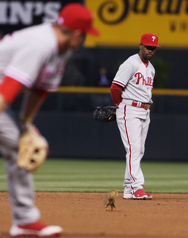 . Philadelphia Phillies third baseman Cody Asche, front, watches as a squirrel, which had been making its rounds around the field, dashes toward Phillies shortstop Jimmy Rollins in the fourth inning of a baseball game against the Colorado Rockies in Denver on Saturday, April 19, 2014. (AP Photo/David Zalubowski)