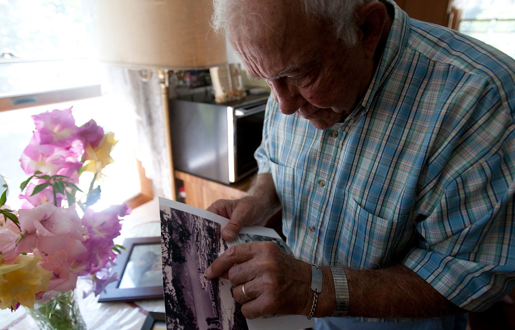 . Herbert Miller of Pulaski, New York, looks at a photograph of the North Korean POW camp he spent three years in during the Korean War. Miller was about to be executed by a North Korean soldier during a the Korean War when his life was saved by Father Emil Kapaun of Pilsen, Kansas. The two spent several months together in a prison camp near the Chinese border.  (Travis Heying/Wichita Eagle/MCT)