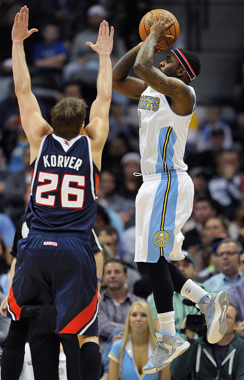 . Denver guard Ty Lawson put up a shot past Atlanta guard Kyle Korver in the second half.     Photo By Karl Gehring/The Denver Post