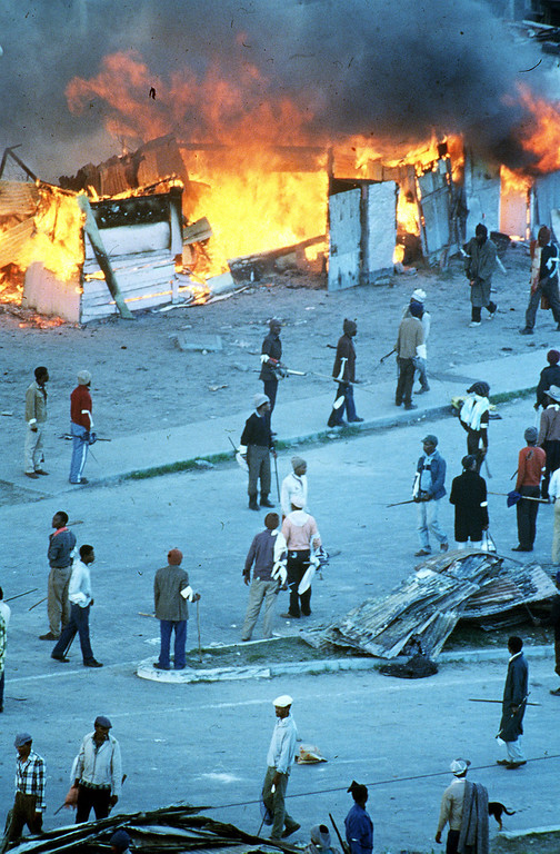 """. Crossroads burning - Vast sections of the Crossroads squatter settlement near Cape Town, home to more than 100,000 people, lay in ruins on May 21, 1986, after four days of raging battles between rival black conservative vigilants and anti-apartheid militants. The death toll is said to have risen to 26 and as many as 50,000 were reported homeless. The U.S. ambassador to South Africa, Herman Nickel called it \"""" a human disaster of major proportions\"""". (AP-Photo/Argus) 21.5.1986"""