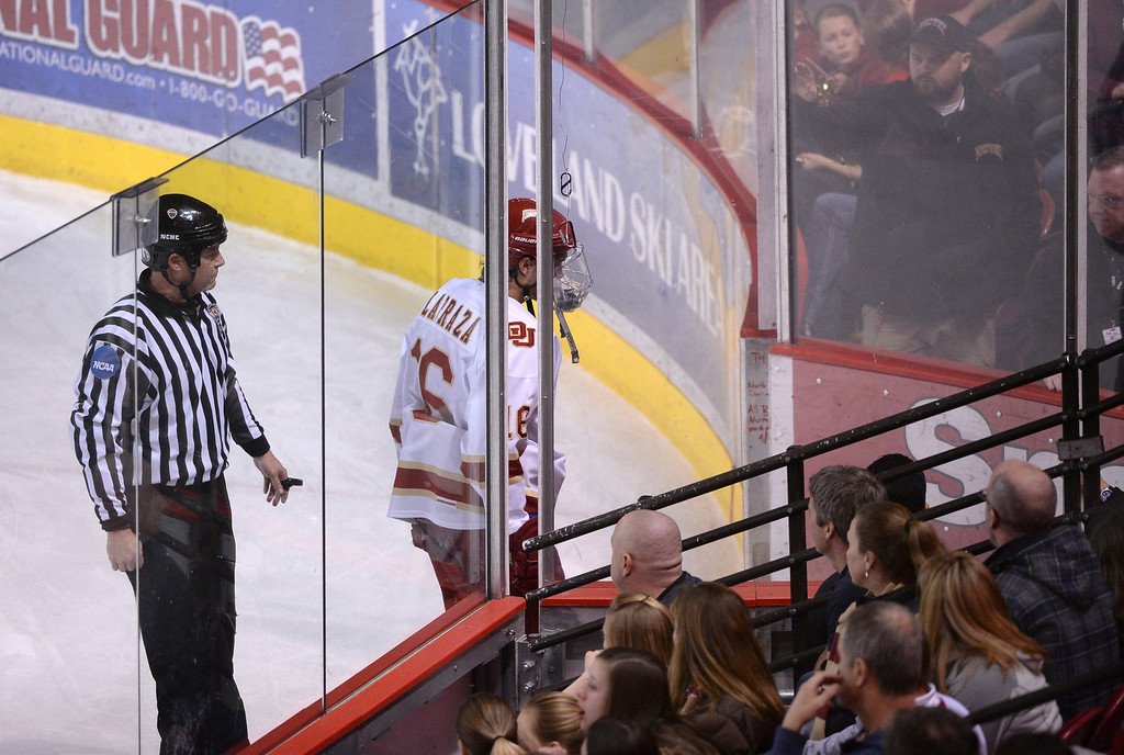 . DENVER, CO. - FEBRUARY 21, 2014: Denver wing Zac Larraza was escorted from the ice following a game misconduct penalty in the second period. The University of Denver hockey team hosted Colorado College at Magness Arena Friday night, February 21, 2014. Photo By Karl Gehring/The Denver Post