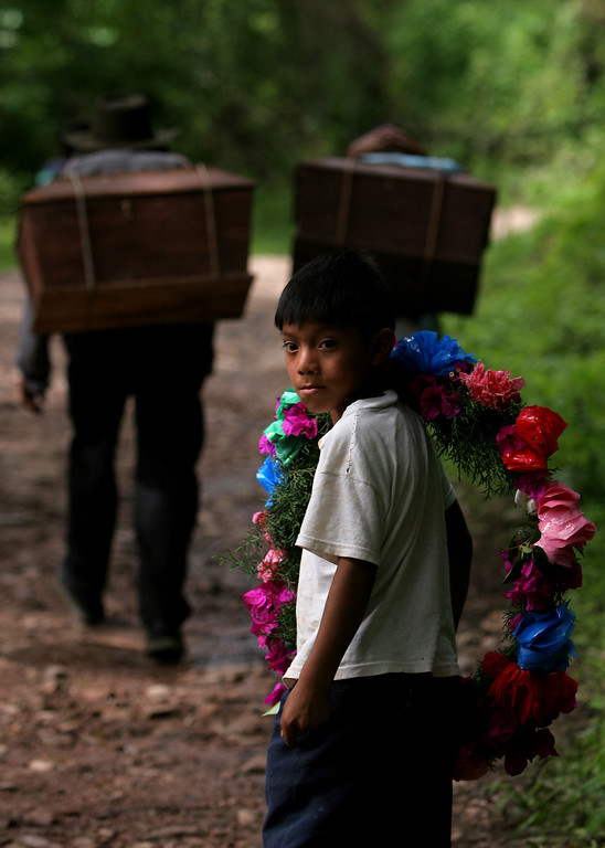. A boy looks on while walking behind two men carrying the remains of relatives towards a cemetery for a reburial ceremony of 19 people missing since the massacres occurred in San Martin Jilotepeque in 1982, in San Martin Jilotepeque, 70 Km (44 miles) west of Guatemala City, Guatemala, on Wednesday, July 12, 2006. According to the United Nations, 426 massacres were reported in Guatemala, mostly during the former dictator Efrain Rios Montt\'s tenure. (AP Photo/Alexandre Meneghini)