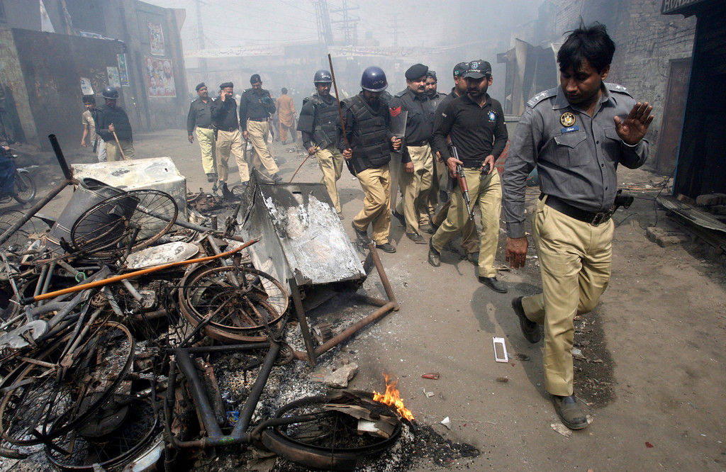 . Pakistani police officers walk past belongings of Christian families, which were burnt by an angry mob, in Lahore, Pakistan, Saturday, March 9, 2013. A mob of hundreds of people in the eastern Pakistani city of Lahore attacked a Christian neighborhood Saturday and set fire to homes after hearing accusations that a Christian man had committed blasphemy against Islam\'s prophet, said a police officer. (AP Photo/K.M. Chaudary)