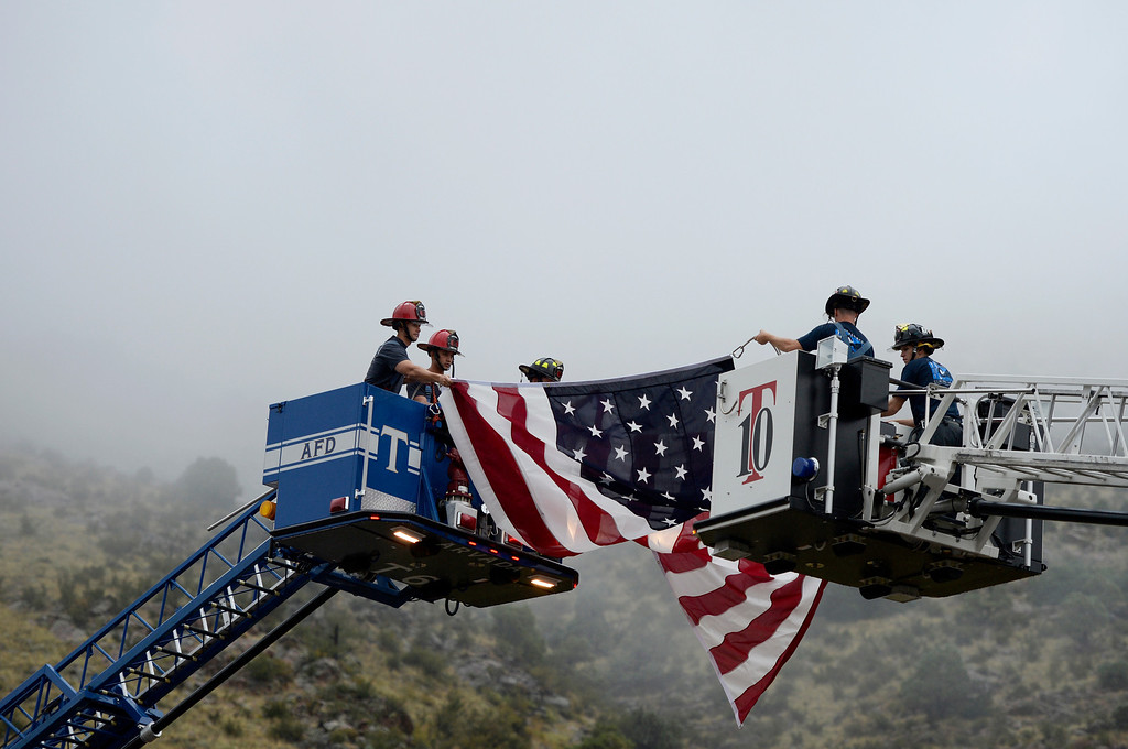. Firefighters from Arvada Fire and West Metro Fire raise a flag at Red Rocks Amphitheater to honor the people and events of 9/11, September 11, 2013. (Photo By RJ Sangosti/The Denver Post)