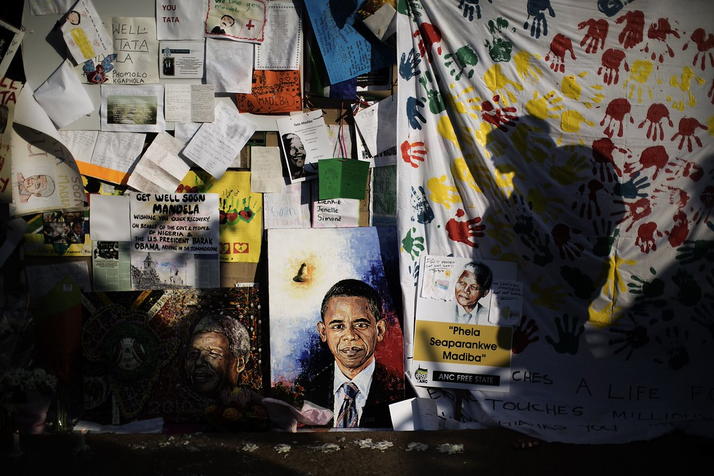 . Shadows are reflected on a wall where a portrait of visiting US President Barak Obama is displayed outside the Mediclinic Heart Hospital where former South African President Nelson Mandela is hospitalized in Pretoria on June 29, 2013. Mandela, who turns 95 next month, has been in intensive care for three weeks for a recurrent lung disease dating from his years in apartheid-era prisons. MARCO LONGARI/AFP/Getty Images