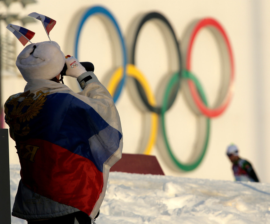 . A fan watches warmups  before the men\'s biathlon 10k sprint, at the 2014 Winter Olympics, Saturday, Feb. 8, 2014, in Krasnaya Polyana, Russia. (AP Photo/Charlie Riedel)