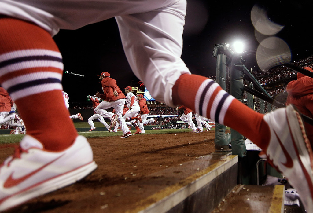 . The St. Louis Cardinals run out of the dugout after Game 6 of the National League baseball championship series against the Los Angeles Dodgers, Friday, Oct. 18, 2013, in St. Louis. The Cardinals won 9-0 to win the series. (AP Photo/Jeff Roberson)