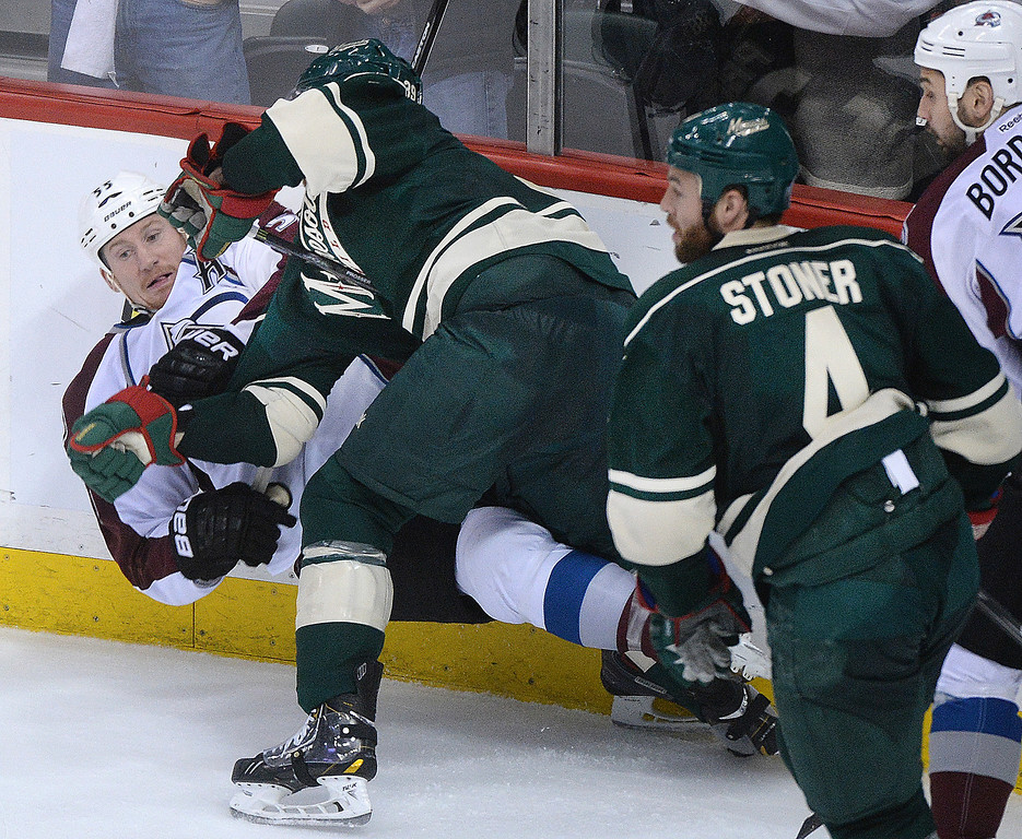 . Minnesota defenseman Nate Prosser pushed Cody McLeod to the ice late in the third period.  (Photo by Karl Gehring/The Denver Post)
