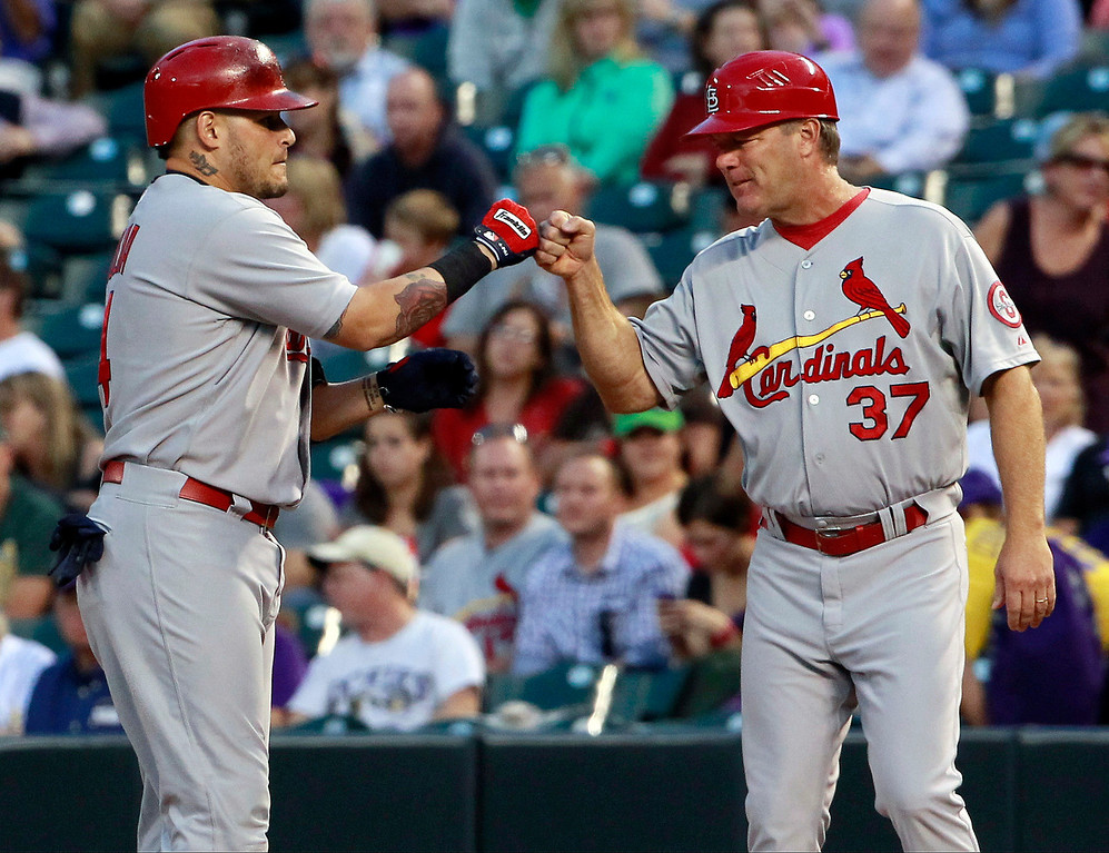 . St. Louis Cardinals\' Yadier Molina, left, is congratulated after his RBI single by first base coach Chris Maloney against the Colorado Rockies in the first inning of a baseball game in Denver on Tuesday, Sept. 17, 2013. (AP Photo/David Zalubowski)