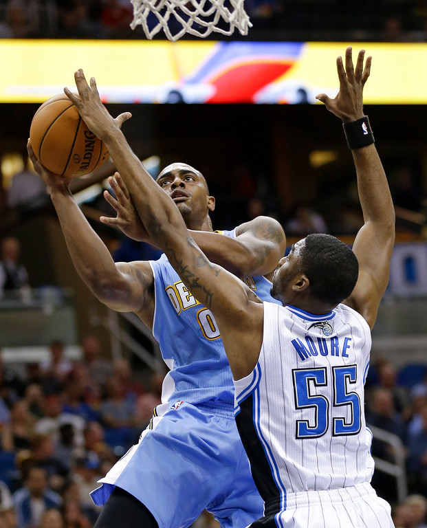 . Denver Nuggets\'s Darrell Arthur, left, goes up for a shot against Orlando Magic\'s E\'Twaun Moore (55) during the first half of an NBA basketball game in Orlando, Fla., Wednesday, March 12, 2014. (AP Photo/John Raoux)