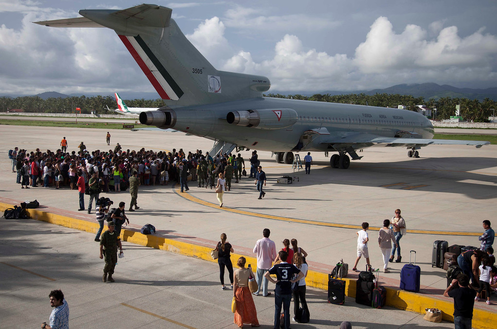 . Hundreds of stranded tourists gather around a Mexican Air Force jet as they wait to be evacuated, at the air base in Pie de la Cuesta, near Acapulco, Mexico, Tuesday, Sept. 17, 2013. With roads blocked by landslides, rockslides, floods and collapsed bridges, Acapulco was cut off from road transport after Tropical Storm Manuel made landfall on Sunday. The airport as well, was flooded. Emergency flights began arriving in Acapulco to evacuate at least 40,000 mainly Mexican tourists stranded in the resort city. (AP Photo/Eduardo Verdugo)
