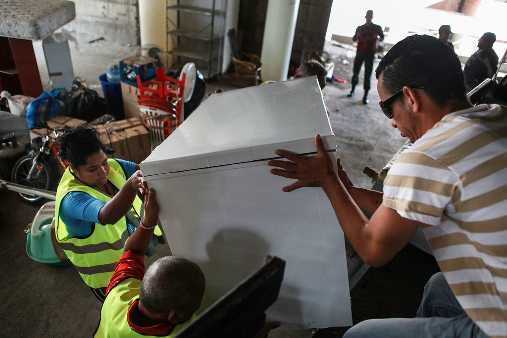 . People load their belongings onto a pick-up truck as they voluntarily leave the Tower of David, an abandoned skyscraper in Caracas originally intended to be an office building that became a \'vertical slum\', during its eviction on July 22, 2014. The government began the eviction and relocation of hundreds of families that were illegally occupying the building. FEDERICO PARRA/AFP/Getty Images