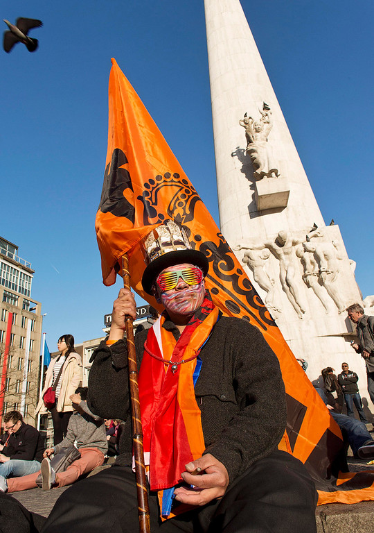 . A man dressed up in orange sits at the Dam square in Amsterdam April 29, 2013. The Royal celebrations in the Netherlands this week put the country and the capital Amsterdam on front pages and television screens around the world with an orange splash. There\'s plenty to see and do in 48 hours in this compact city, where the world-famous Rijksmuseum only recently reopened after an extensive renovation. Picture taken April 29, 2013. REUTERS/Michael Kooren