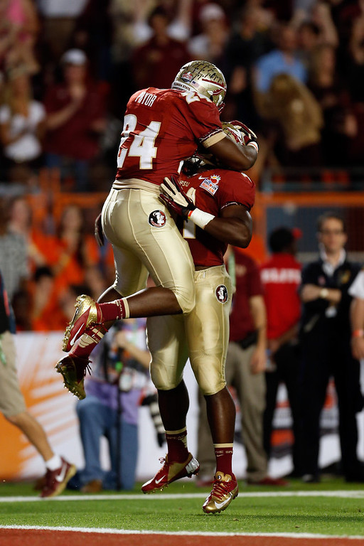 . (L-R)  Lonnie Pryor #24 and Chad Abram #41 of the Florida State Seminoles celebrate after Pryor scored a 60-yard rushing touchdown in the first quarter against the Northern Illinois Huskies during the Discover Orange Bowl at Sun Life Stadium on January 1, 2013 in Miami Gardens, Florida.  (Photo by Chris Trotman/Getty Images)