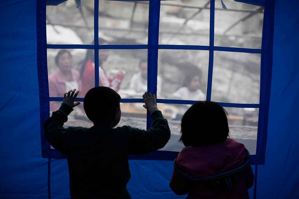 . Children look out from inside a tent after Saturday\'s earthquake in Lingguan town of Baoxing county, Sichuan province April 22, 2013. REUTERS/Aly Song